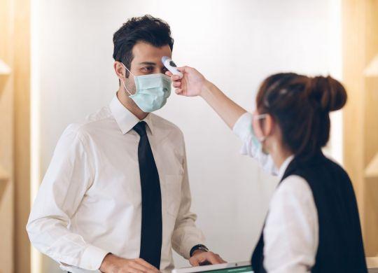 Hotel worker scanning temperature of fellow hotel employee